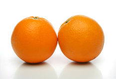 A pair of juicy oranges. Side by side over a white background. Look at my gallery for more fruits and vegetables Stock Photos