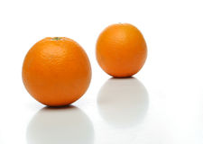 A pair of juicy oranges. One on front and one backwards over a white background. Look at my gallery for more fruits and vegetables royalty free stock photo