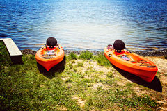 A pair of kayaks at the edge of a sunlit lake Royalty Free Stock Images