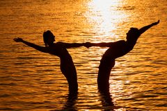Pair Keeps For Hands In Sea On Sunset Royalty Free Stock Photography