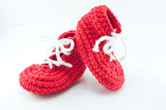Pair of knitted, bright red baby booties. A pair of knitted, bright red baby booties Royalty Free Stock Image
