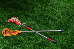 A pair of lacrosse sticks laying on a field Stock Photography