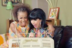 Pair of Ladies Laughing at TV Stock Image
