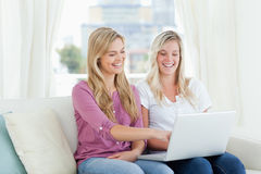 A pair of laughing women sitting on the couch with a laptop in h Royalty Free Stock Photo