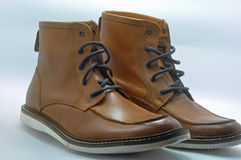 Pair of leather boots. A brand new pair of brown leather walking boots with laces, blue background Royalty Free Stock Photography