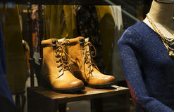 A pair of  Leather boots and a female mannequin in a fashion shop window Royalty Free Stock Image