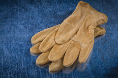 Pair of leather brown protective gloves on scratched metallic ba Royalty Free Stock Images