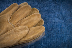 Pair of leather brown protective gloves on scratched metallic su Stock Photo