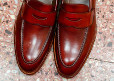 Pair of leather cherry calf penny loafer shoes on the stone floor together one by one closely. Close up. Pair of leather burgundy penny loafer shoes together on Stock Photo