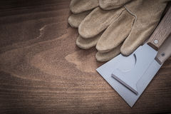 Pair of leather protective gloves and glossy paint scrapers Royalty Free Stock Images