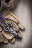 Pair of leather protective gloves sharp metal secateurs and hank Stock Image