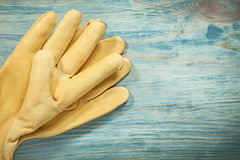 Pair of leather protective gloves on wooden board construction c Royalty Free Stock Photos