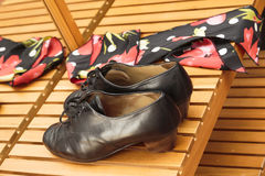 Pair of leather shoes used in flamenco dancing. Pair of low heeled brown leather shoes and a colorful scarf used in flamenco dancing lying on a wooden bench in Royalty Free Stock Photo