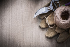 Pair of leather working gloves secateurs and hank of twine on wo Stock Image