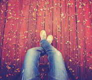 A pair of legs taken from overhead on a deck with leaves that ha Stock Photo