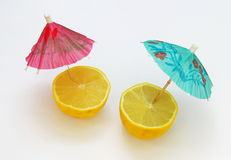 A pair of lemons with cocktail umbrellas. Two ripe yellow lemons decorated with cocktail umbrellas, as if having holidays themselvees royalty free stock image