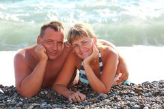 Pair lie on pebble beach Stock Photography