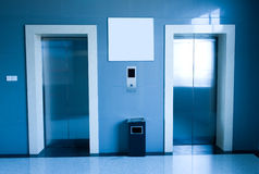 A pair lifts. In a hotel hall, blue tone Royalty Free Stock Image