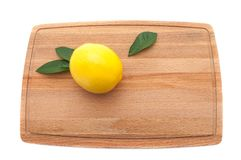 A pair of limes and a lemon wait to be cut on a worn butcher blo stock photo