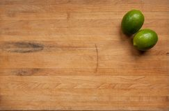 Pair of limes on a worn cutting board stock image