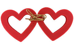 Pair of linked hearts. Two red hearts bound by cord on white background Stock Photos