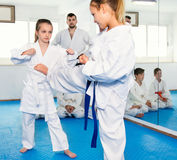 Pair of little girls practicing new karate moves during class Royalty Free Stock Image