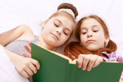 Pair of little girls reading book Stock Image