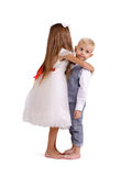 Cute, fancy, charming brother and sister isolated on a white background. Little boy and girl hugging. Family concept. Royalty Free Stock Images