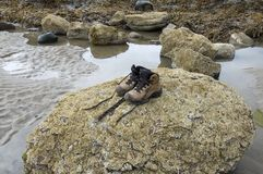 Pair of lonely hiking boots. On beach Stock Photos