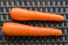 Pair long fresh raw carrot on brown plastic rattan weave table. Close up Royalty Free Stock Photo