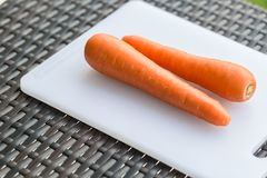 Pair long fresh raw carrot on a plastic cutting board is white color. Royalty Free Stock Photo