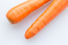 Pair long fresh raw carrot on a plastic cutting board is white color. Stock Photo