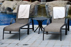 A pair of lounge chairs by a pool Royalty Free Stock Photos