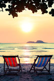 Pair of lounge chairs on sunset at beach. Nature. Royalty Free Stock Photo