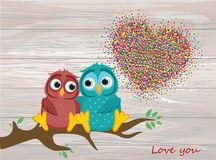 A pair of lovely owls in love, sit on a branch. Colorful confett. I in the shape of heart. Greeting card for Valentine`s Day and invitation to the wedding Royalty Free Stock Images