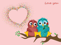 A pair of lovely owls in love, sit on a branch. Colorful confetti. In the shape of heart. Greeting card for Valentine`s Day and invitation to the wedding. The Royalty Free Stock Photo