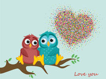 A pair of lovely owls in love, sit on a branch. Colorful confetti. In the shape of heart. Greeting card for Valentine`s Day and invitation to the wedding. The Stock Photo