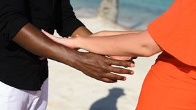 A pair of lovers on the beach. They differ from each other, hands close-up stock video