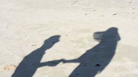 A pair of lovers on the beach. The shadows on the sand stock video