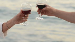 Pair of lovers clink glasses with red wine on the background of the sea. Close-up stock video footage