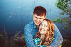 Pair of lovers embracing and laughing at the lake. Loving couple in an embrace laughing while sitting by the lake Royalty Free Stock Photography