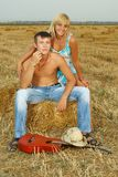 A pair of lovers in the hay with guitar Royalty Free Stock Photography