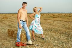 A pair of lovers in the hay with guitar Royalty Free Stock Photo