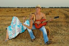 A pair of lovers in the hay with guitar Stock Images