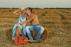 A pair of lovers in the hay with guitar Stock Image