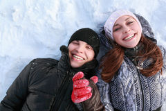 Pair of lovers people lies on snow and laugh Royalty Free Stock Photos