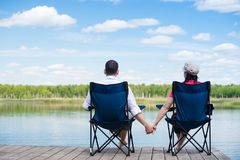Pair of lovers sit on the pier and look at nature stock photo
