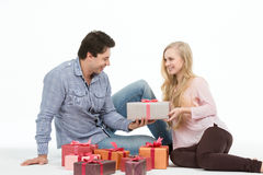 A pair of lovers sitting on the floor and give each other gifts. Holidays. Stock Photo