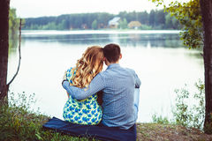 Pair of lovers sitting on the shore  the lake turned away. Royalty Free Stock Photo
