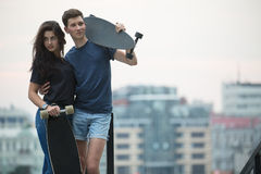 Pair of lovers teen is posing for the camera. In an embrace with two longboard. Against the background of the urban landscape Royalty Free Stock Images